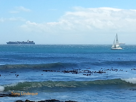 A large ship and a yacht seen from Glencairn Beach in False Bay