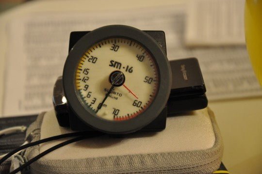 Analogue depth gauge with red needle showing maximum depth
