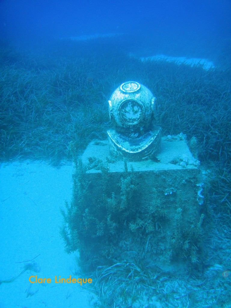 The helmet rests on a plinth, raising it off the seabed