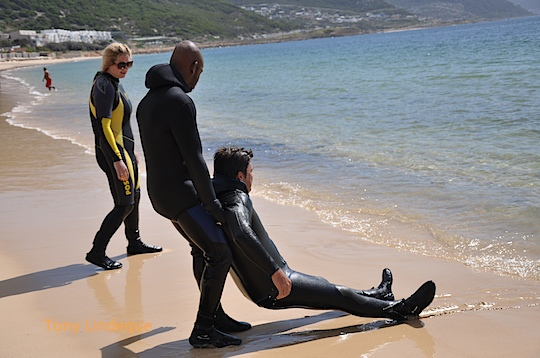 Dinho drags Craig up the beach while Kate looks on helpfully