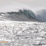 A surfer is dwarfed by the wave