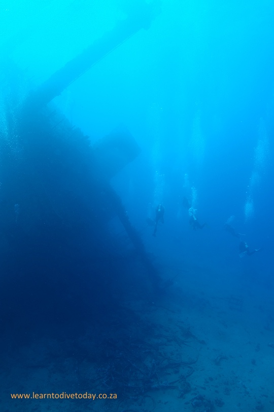 Divers next to the tilted wreck